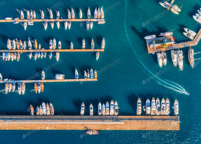 Aerial view of amazing boats at sunset. Minimalistic landscape
