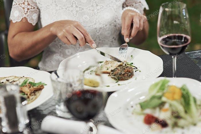 Женщина режет на пищу на ломтиках. Овощная еда находится на столе вне ресторана