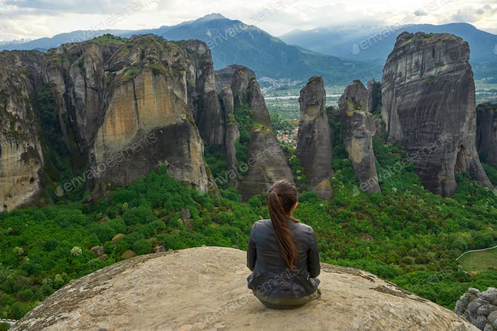Girl enjoys the view of great and high rock in Meteora, Thessaly