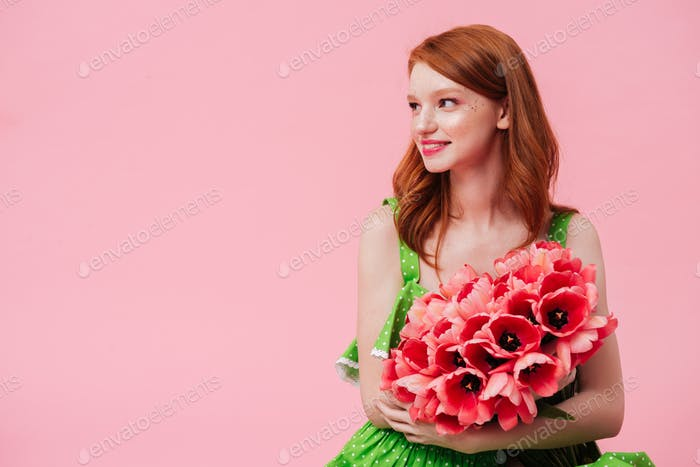 Pretty smiling woman holding bouquet of flowers