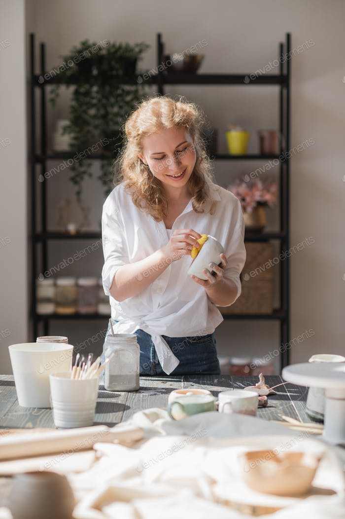 Young woman at pottery studio wiping unnecessary glaze paint with a sponge