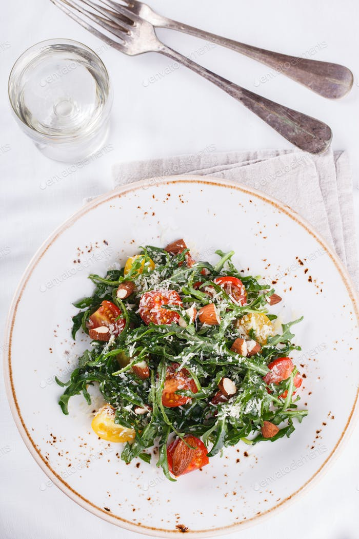 Salad cherry tomatoes with arugula and Parmesan