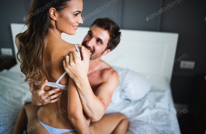 Attractive sexy woman with her handsome partner in bedroom