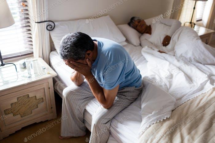 Angespannter Senior Mann sitzt auf dem Bett