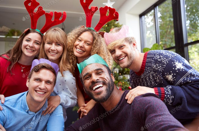 Retro Style Shot Of Group Of Friends Enjoying Christmas Party At Home Together Taking Selfie