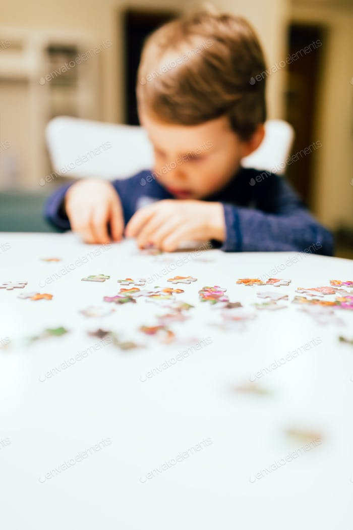 2 year old child solving jigsaw puzzle