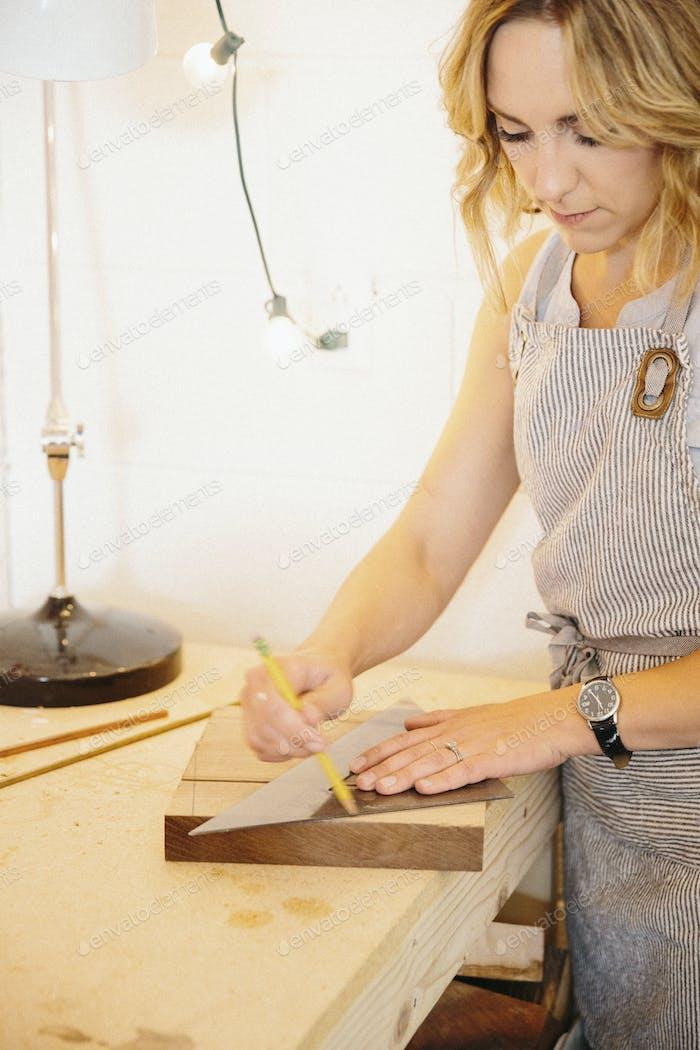 Eine Frau in ihrer Werkstatt mit einer Vorlage, um Holzblöcke zu markieren.