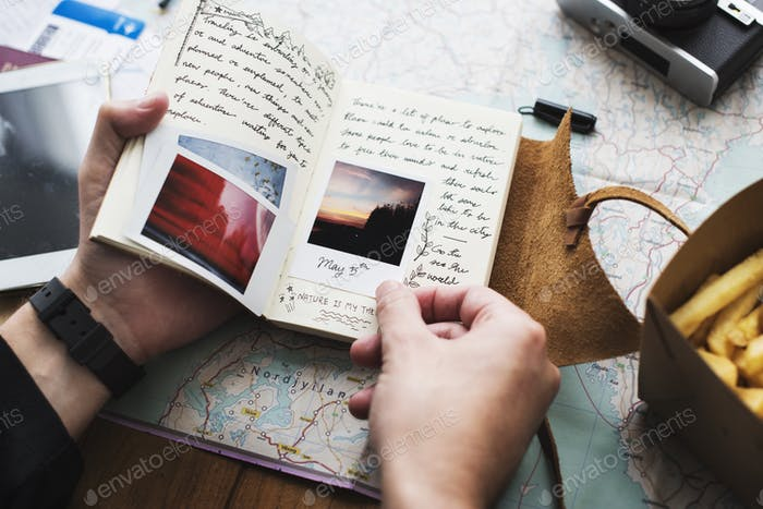 Closeup of hands holding journey diary notebook over map backgro