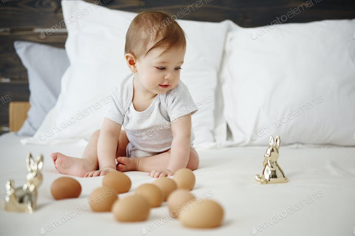 Baby playing with egg on the bed