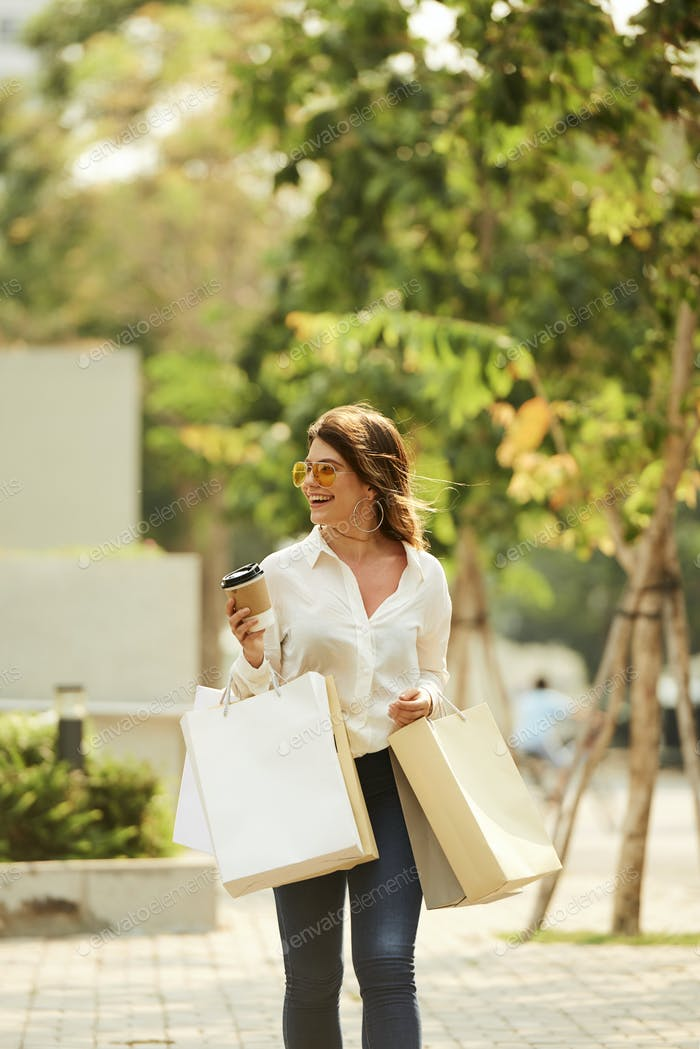 Cheerful young woman with paper-bags