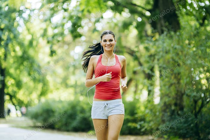 Young beautiful athlete jogging in park
