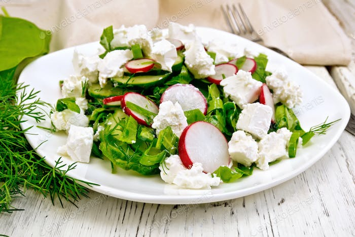 Salad with cheese and radishes in plate on board