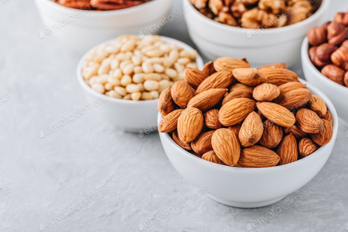 Almonds, pecans, walnuts, pine nuts and hazelnuts in white bowls on grey background.