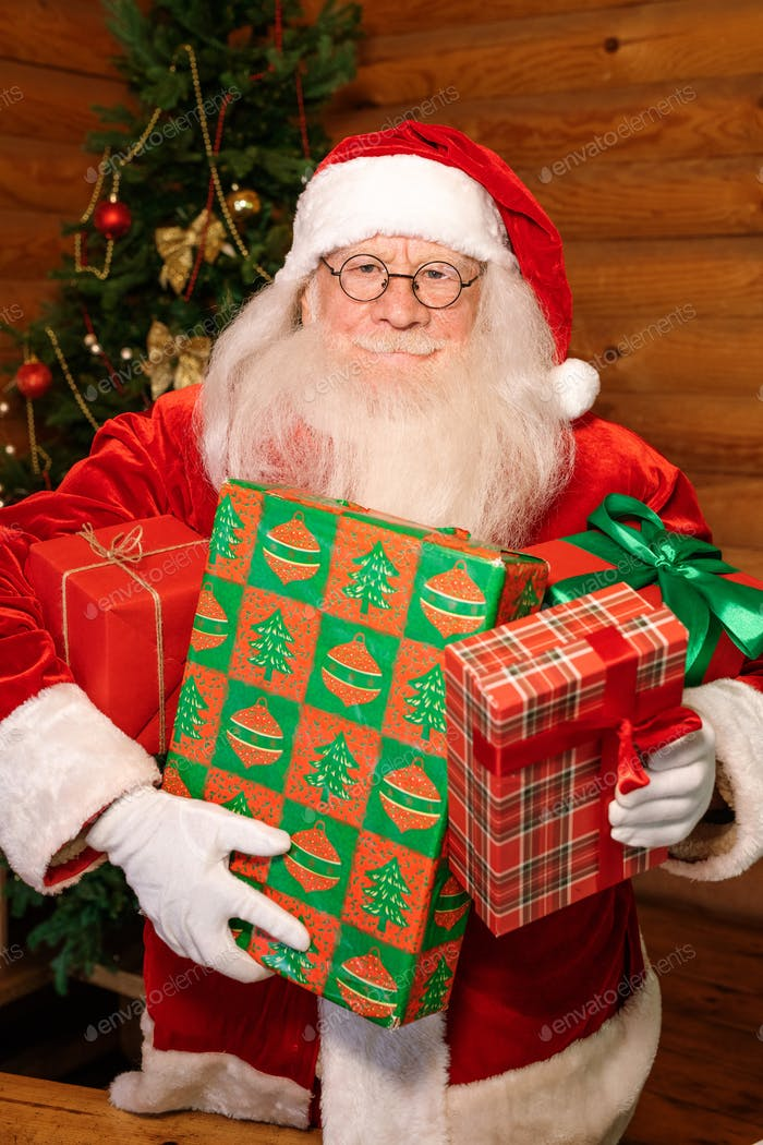 Happy Santa with four packed giftboxes standing in front of camera