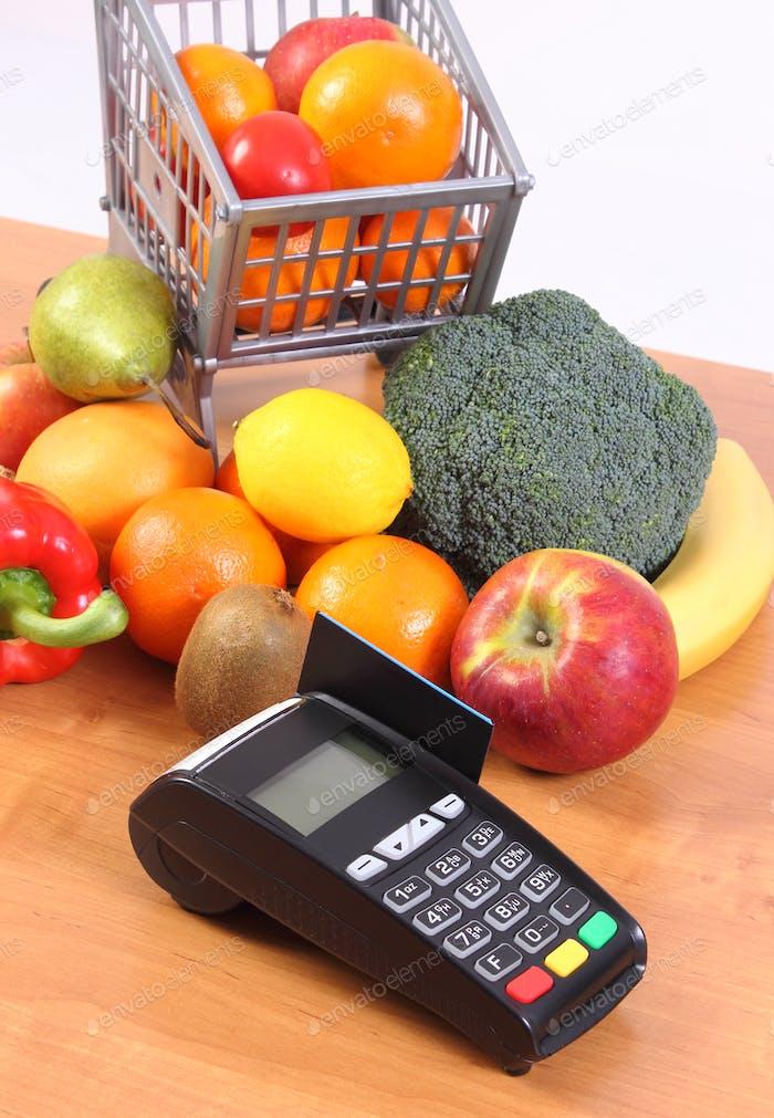 Zahlungsterminal mit Kreditkarte, Obst und Gemüse. Bargeldloses Bezahlen für Einkaufskonzept