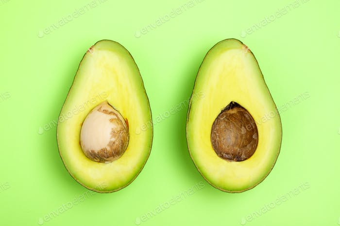Avocado slices on the green background