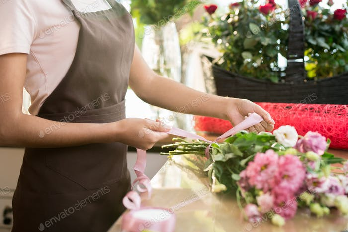 Tying up silk ribbon around bouquet
