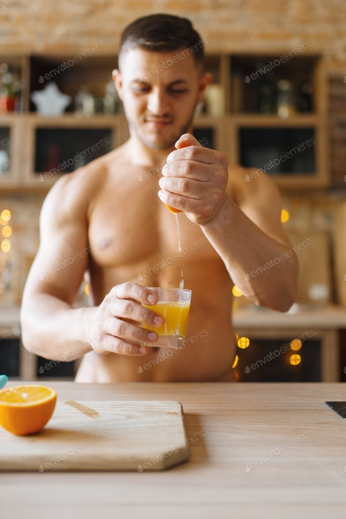 Muscular man with naked body cooking orange juice