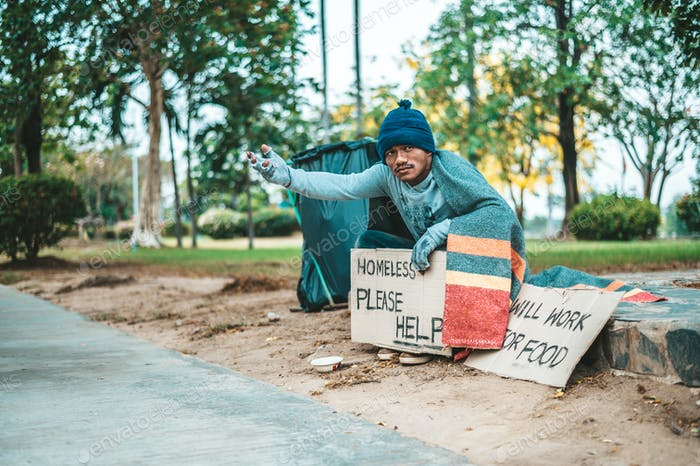 a man sitting beggars with homeless please help message.