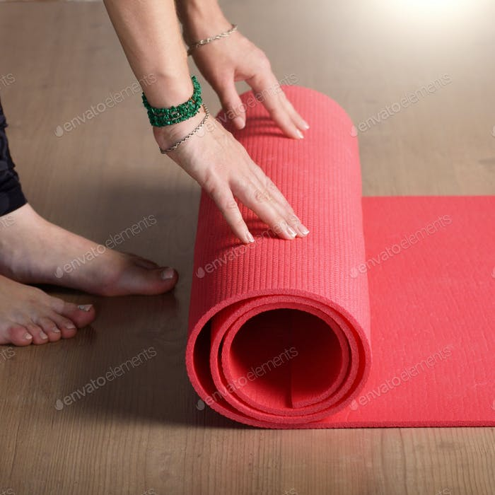 Female hands unrolling yoga mat before workout exercise. Healthy