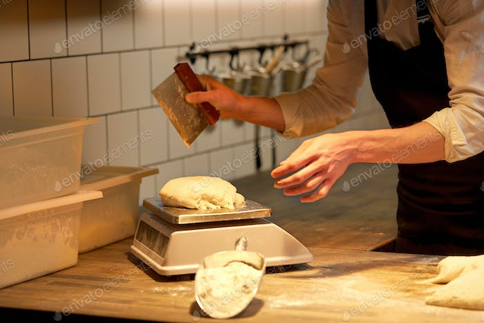 chef or baker weighing dough on scale at bakery