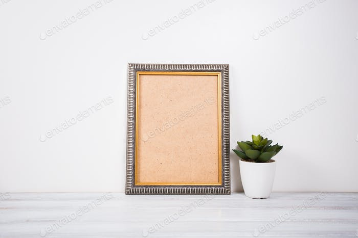 Blank white frame and plant on wooden surface. Mock up