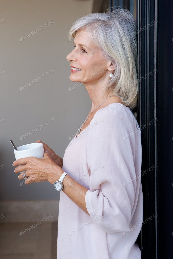 smiling older woman standing in home drinking coffee