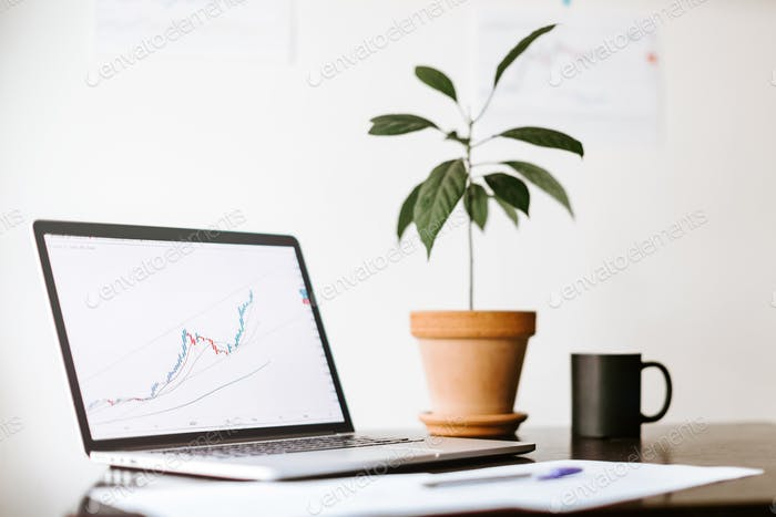 workplace of stock trader with laptop in minimalistic style