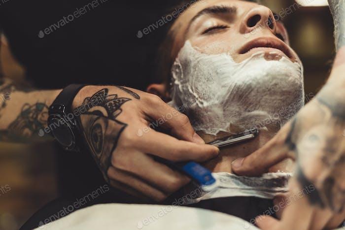 Barber shaving client