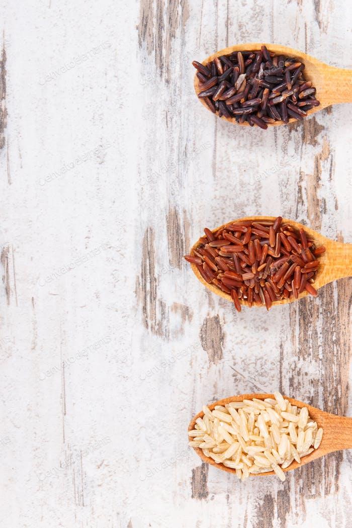 Brauner, schwarzer und roter Reis auf Holzlöffel, gesundes glutenfreies Lebensmittelkonzept, Kopierraum für Text