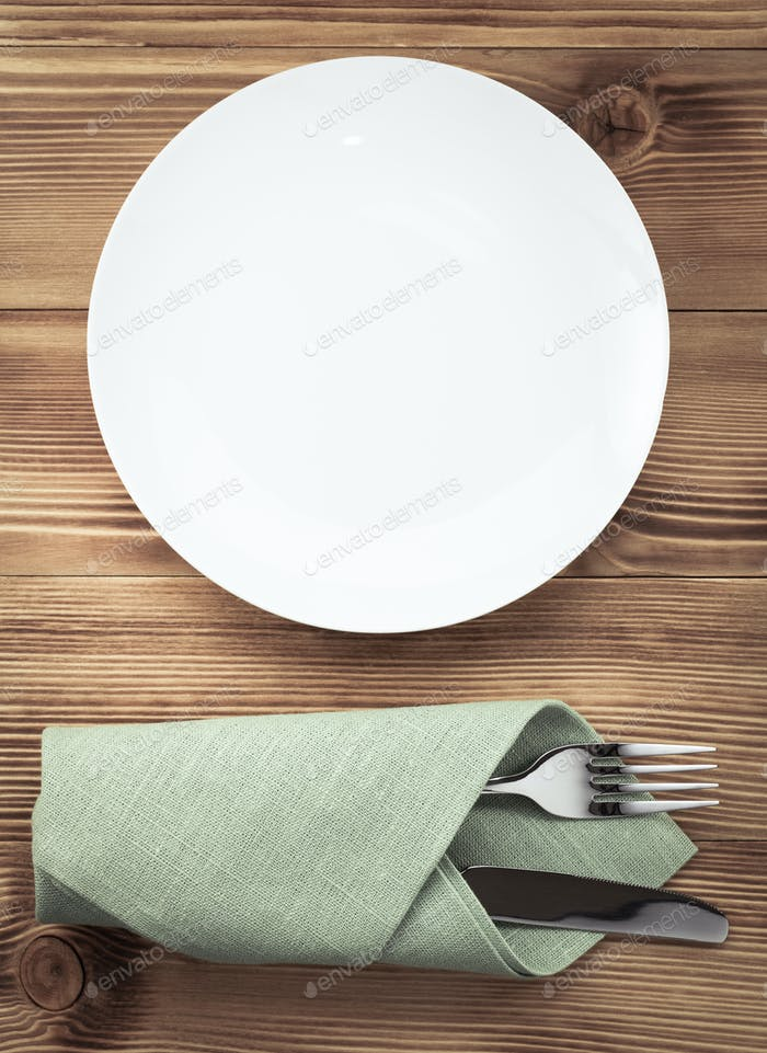 knife and fork with napkin on wood