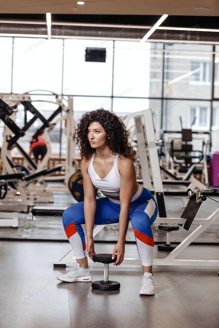 Ziemlich schlankes Mädchen mit dunklen lockigen Haar in einem Sportbekleidung gekleidet ist tun zurück Kniebeugen mit schweren