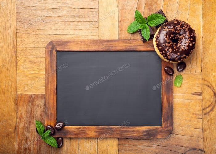 Black chalkboard with chocolate glazed donut