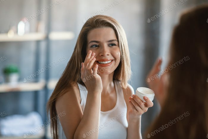 Joyful millennial lady applying facial cream in front of mirror at home