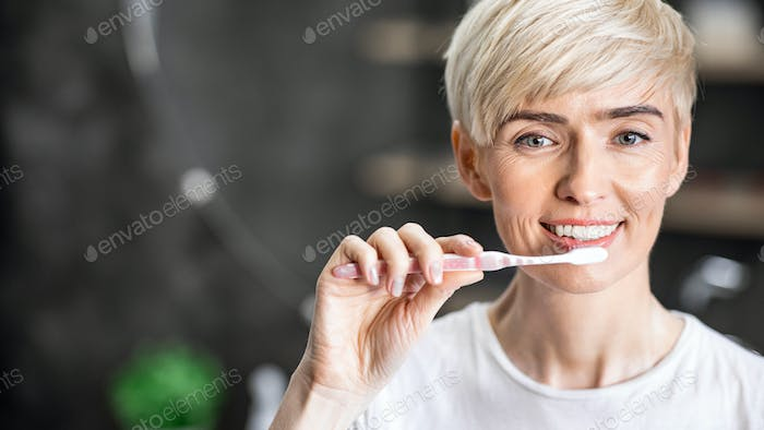 Cheerful Lady Cleaning Teeth In Morning Using Toothbrush In Bathroom