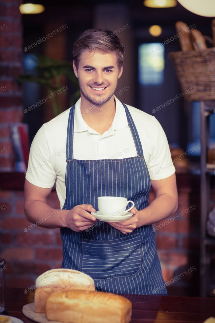 Portrait of a barista holding a cup of coffee at the coffee shop