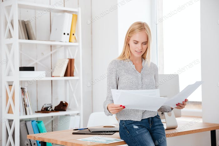 Businesswoman sitting on the office desk and reading documents