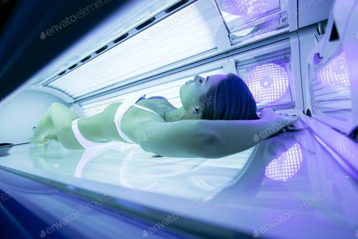 Beautiful young and sexy woman tanning in solarium