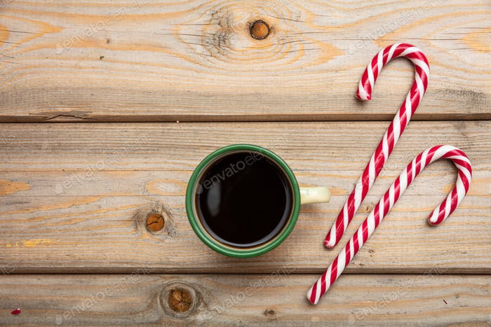 Candy canes and a cup of coffee on wooden background, copy space, top view