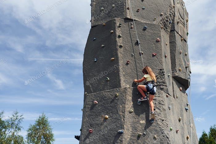 Little girl in casual white clothes training rock climbing outdoors