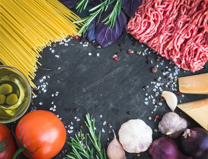 Spaghetti Bolognese ingredients on a dark stone background with