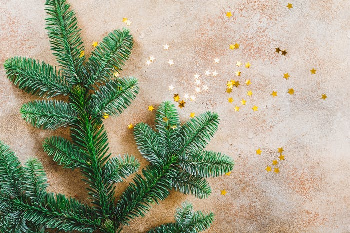 Fir branch and golden glitter stars confetti on a beige background. Christmas and New Year concept.
