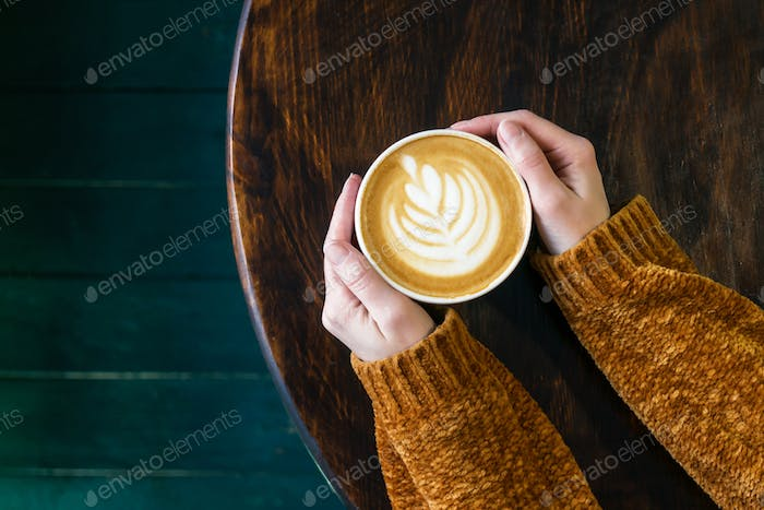 Cup of cappuccino with latteart in hands.