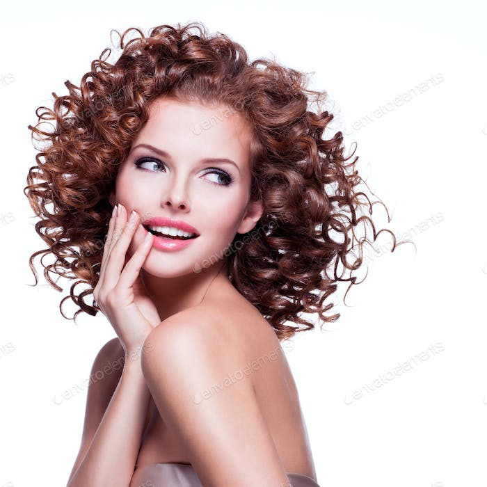 Beautiful smiling thoughtful woman with curly hair.