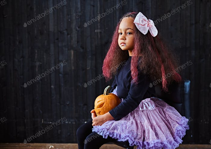 Thumbnail for ittle girl dressed in trendy scary dress holds pumpkin while sitting on chair in dark house.