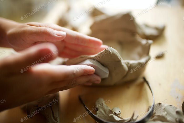 Close up young girl hands molding clay