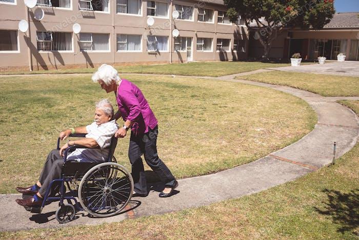 Side view of senior Caucasian woman pushing senior man on wheelchair at backyard nursing park
