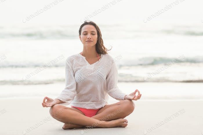 Sporty brunette sitting in lotus pose on the beach