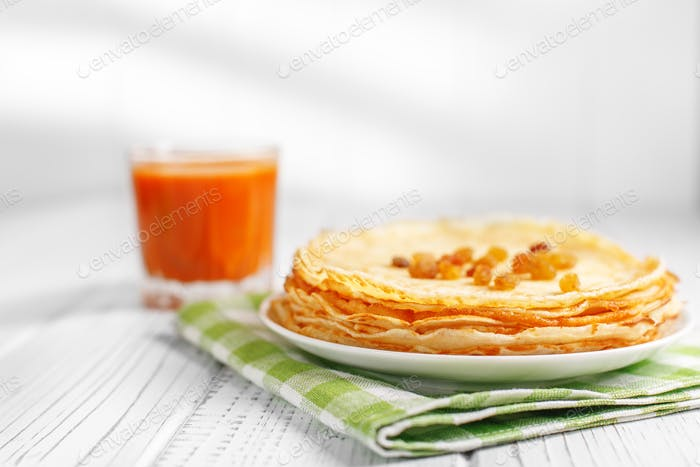 Delicious pancakes with raisins and carrot juice. The concept of
