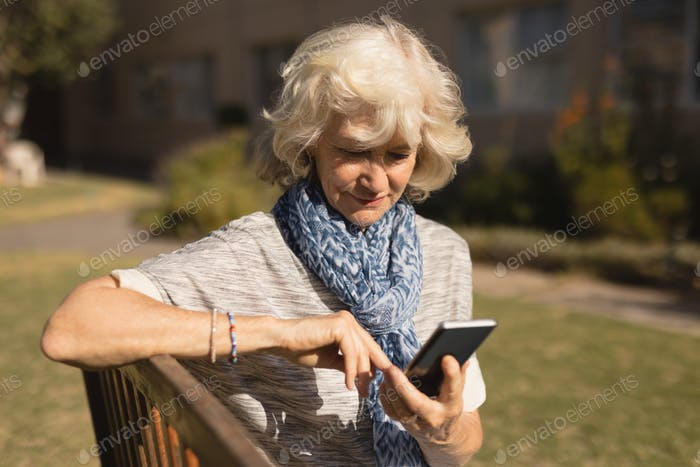 Side view of active senior Caucasian woman using mobile phone in the park